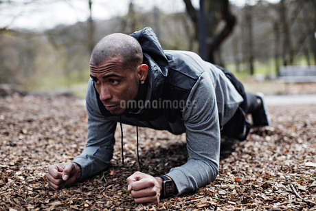 Determined male athlete performing plank position in forestの写真素材 [FYI02140756]