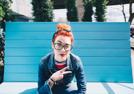 Portrait of redhead young woman gesturing peace sign while sitting on benchの写真素材 [FYI02140766]