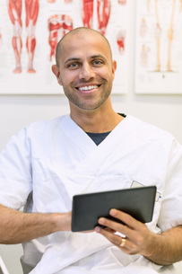 Portrait of happy doctor holding digital tablet in orthopedic clinicの写真素材 [FYI02140768]