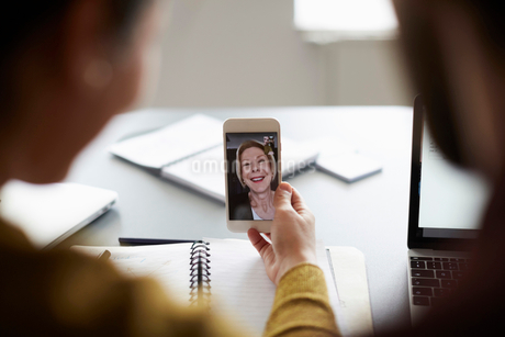 High angle view of colleagues video conferencing with senior businesswoman on smart phone in board rの写真素材 [FYI02140801]