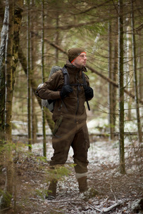 Thoughtful male hiker carrying backpack while standing in woodland during winterの写真素材 [FYI02140823]