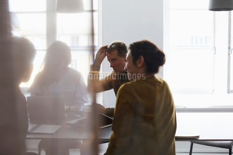 Creative team sitting in board room seen from glass at officeの写真素材 [FYI02140840]