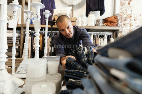 Male owner arranging jeans on table by candles at clothing storeの写真素材 [FYI02140925]
