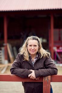 Portrait of female farmer leaning on fenceの写真素材 [FYI02140973]