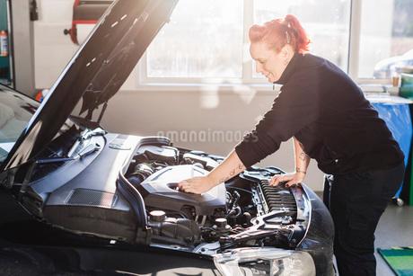 Female mechanic repairing car in auto repair shopの写真素材 [FYI02140996]