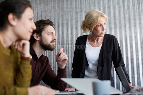 Senior businesswoman with mid adult colleagues looking away in board roomの写真素材 [FYI02140998]