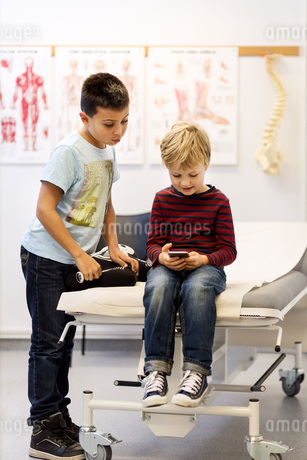 Brothers using smart phone at examination table in orthopedic clinicの写真素材 [FYI02140999]