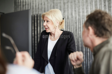 Senior female professional standing with colleagues in board room during meetingの写真素材 [FYI02141005]