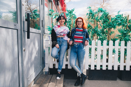 Portrait of hipster female friends standing against fence by buildingの写真素材 [FYI02141060]