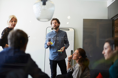 Businessman and businesswoman giving presentation to colleagues in board room at creative officeの写真素材 [FYI02141066]