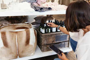 Owner using digital tablet while checking bottles on shelf at storeの写真素材 [FYI02141078]