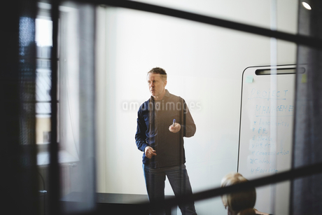 Businessman standing against white wall in board room seen from glass at creative officeの写真素材 [FYI02141079]