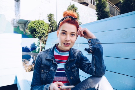 Portrait of redhead young woman using mobile phone while sitting on benchの写真素材 [FYI02141087]
