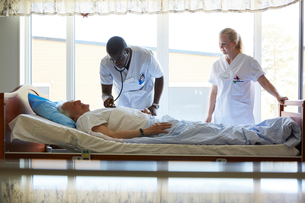 Female nurse looking at male colleague examining senior man lying on bed in hospital wardの写真素材 [FYI02141154]