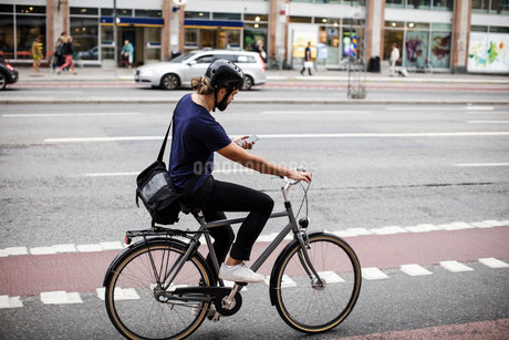 Full length of man using phone while cycling on city streetの写真素材 [FYI02141161]