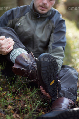 Male hiker removing boot while sitting in forestの写真素材 [FYI02141176]