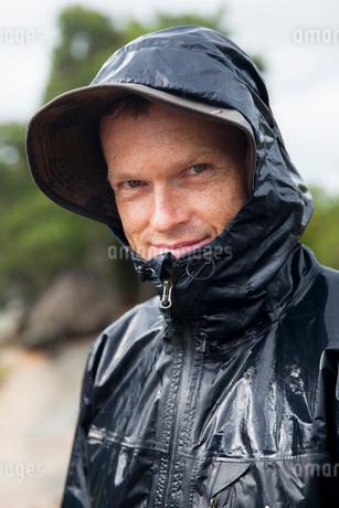 Portrait of smiling man wearing raincoatの写真素材 [FYI02141198]