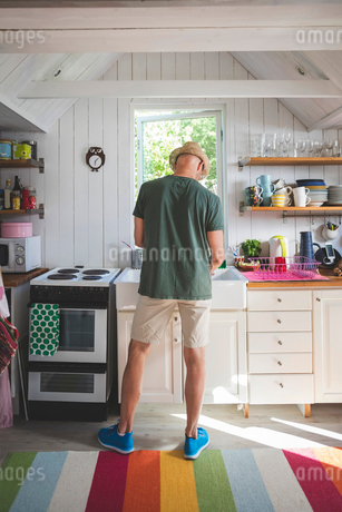 Rear view of man working in kitchen at homeの写真素材 [FYI02141206]