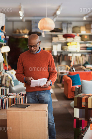 Senior man reading document with digital tablet at storeの写真素材 [FYI02141304]