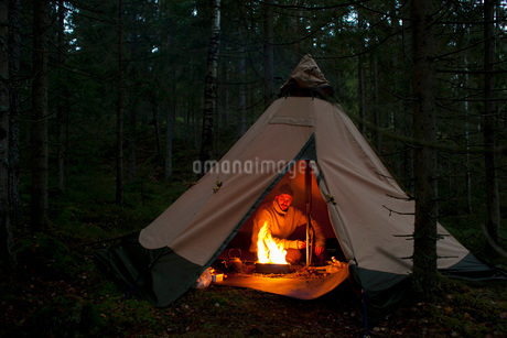 Mid adult man sitting by campfire in tent at woodland during nightの写真素材 [FYI02141340]