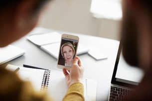 Colleagues video conferencing with senior businesswoman on smart phone in board roomの写真素材 [FYI02141346]