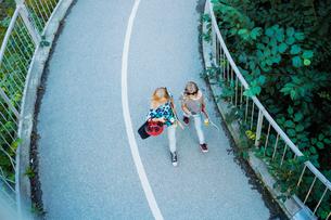 High angle view of girls walking on bridge amidst treesの写真素材 [FYI02141386]