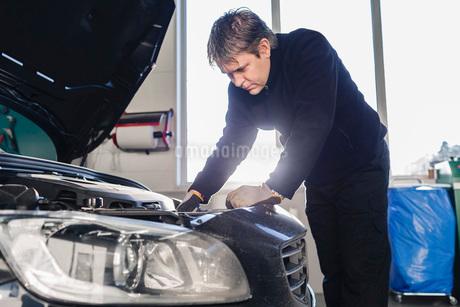 Mechanic repairing car in auto repair shopの写真素材 [FYI02141417]