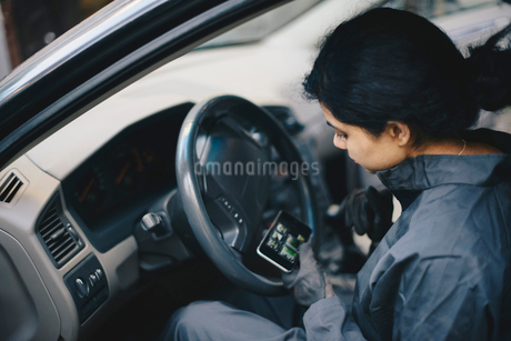 Female mechanic using mobile phone while sitting in carの写真素材 [FYI02141451]