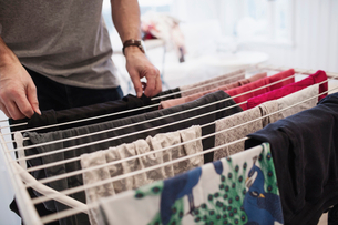 Midsection of man drying clothes on rack at homeの写真素材 [FYI02141453]