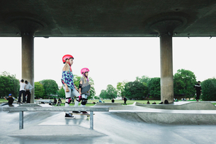 Side view of friends standing at skateboard park against clear skyの写真素材 [FYI02141462]