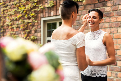 Happy lesbian couple looking at each other during wedding ceremony against wallの写真素材 [FYI02141467]