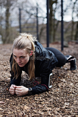 Determined female athlete performing plank position in forestの写真素材 [FYI02141479]