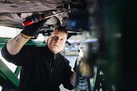 Female mechanic examining car with hammer in auto repair shopの写真素材 [FYI02141503]
