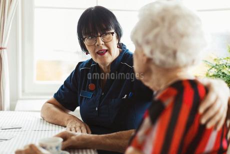 Caretaker talking to senior woman at homeの写真素材 [FYI02141509]