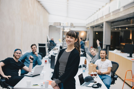 Portrait of happy female computer programmer with colleagues sitting at desk in backgroundの写真素材 [FYI02141513]