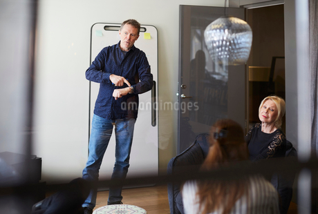 Businessman pointing at wristwatch while standing in board room with female colleagues seen from glaの写真素材 [FYI02141532]