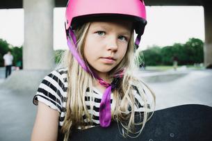 Portrait of girl wearing pink helmet holding skateboard at parkの写真素材 [FYI02141537]