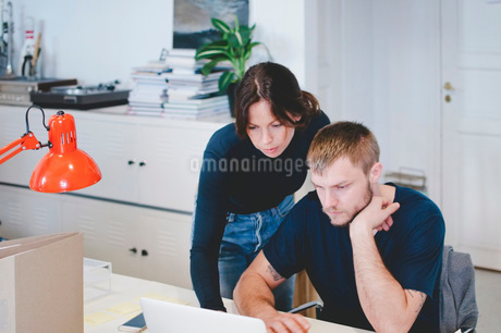 Business people using laptop at desk in creative officeの写真素材 [FYI02141548]