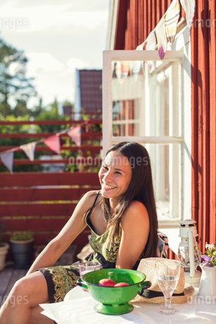 Cheerful woman sitting at table in back yard on sunny dayの写真素材 [FYI02141561]