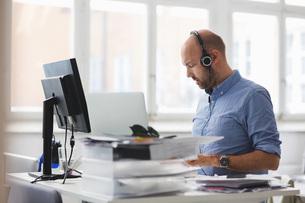 Businessman wearing headphones working at desk in officeの写真素材 [FYI02141564]