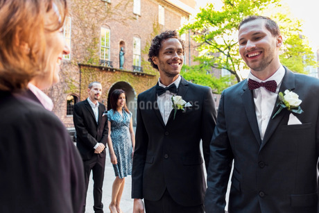 Happy gay couple standing in front of priest with guest in background during wedding ceremonyの写真素材 [FYI02141589]