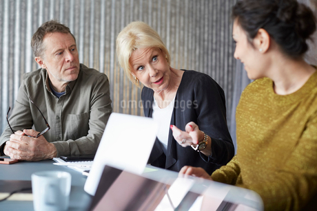 Senior businesswoman discussing with colleagues in board roomの写真素材 [FYI02141652]