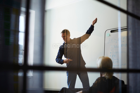 Businesswoman looking at male professional giving presentation against wall in board room seen fromの写真素材 [FYI02141696]