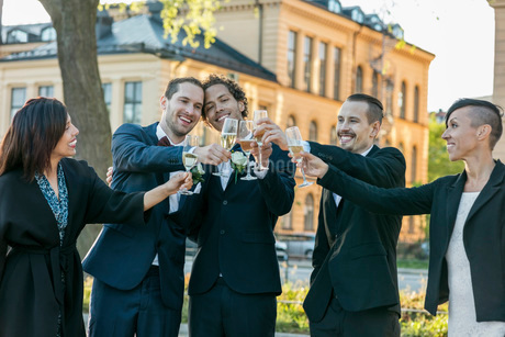 Happy friends raising champagne flutes for toast during wedding ceremonyの写真素材 [FYI02141713]