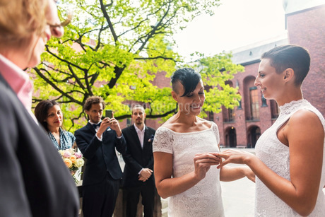 Happy lesbian women exchanging rings during wedding ceremonyの写真素材 [FYI02141728]