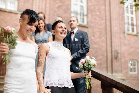 Low angle view of happy lesbian couple on staircase with guests in backgroundの写真素材 [FYI02141752]