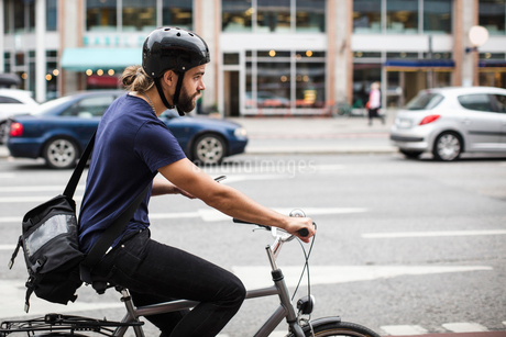 Side view of man cycling on city streetの写真素材 [FYI02141762]