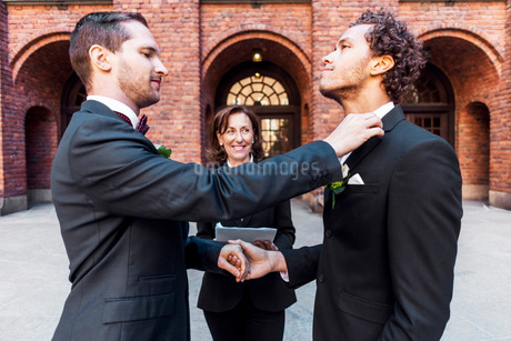 Man adjusting bow tie of gay partner in front of priest during wedding ceremonyの写真素材 [FYI02141777]