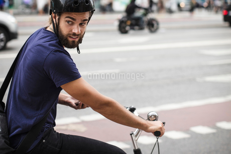 Man wearing helmet cycling on city streetの写真素材 [FYI02141802]