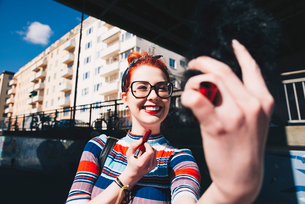 Young woman looking at mobile phone while applying lipstick in cityの写真素材 [FYI02141810]